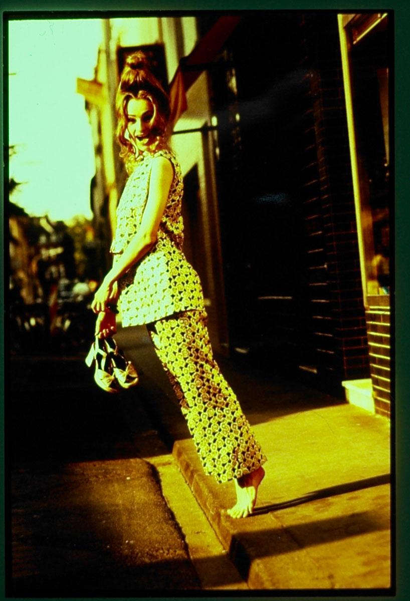 Eine Frau mit einer extravaganten Frisur und einem gemusterten outfit blickt in die kamera. sie trägt keine Schuhe und hat diese in der Hand. Fotograf: Jörg Saibou, Köln Ehrenfeld