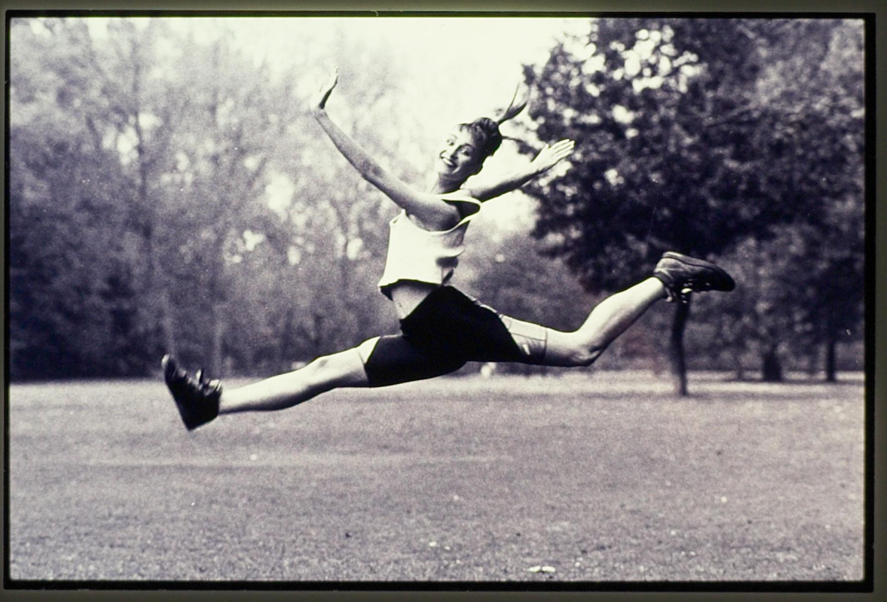 Eine Frau springt mit gestreckten Beinen über eine Wiese. Sie trägt Sportkleidung. Ein Mann mit Kontrabass. Er blickt nach unten. Das Bild ist analog in schwarzweiss aufgenommen. Fotograf: Jörg Saibou, Köln Ehrenfeld