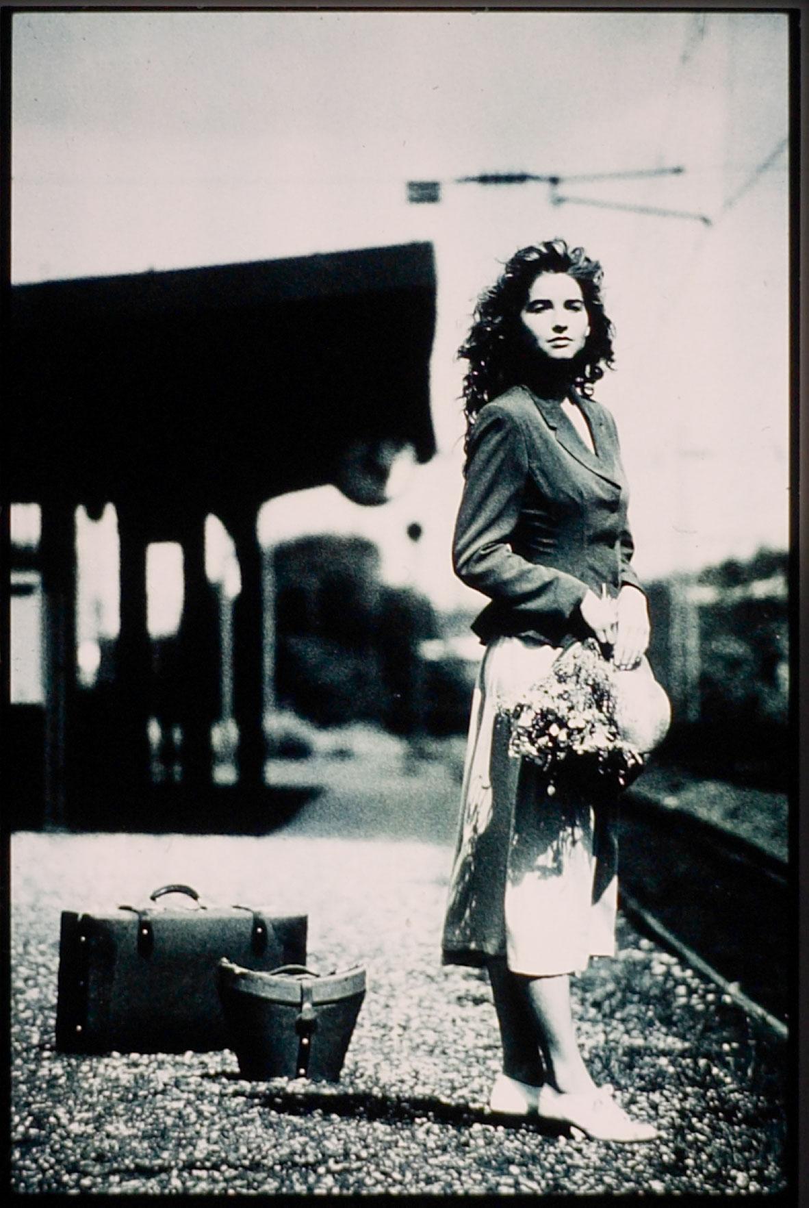 Eine junge Frau steht an einem Bahnhof. Sie trägt einen schwarzen Blazer und einen weißen Rock. Im hintergrund sieht man 2 Taschen. Das Foto ist analog aufgenommen und Schwarzweiss vergrößert. Fotograf: Jörg Saibou, Köln Ehrenfeld.