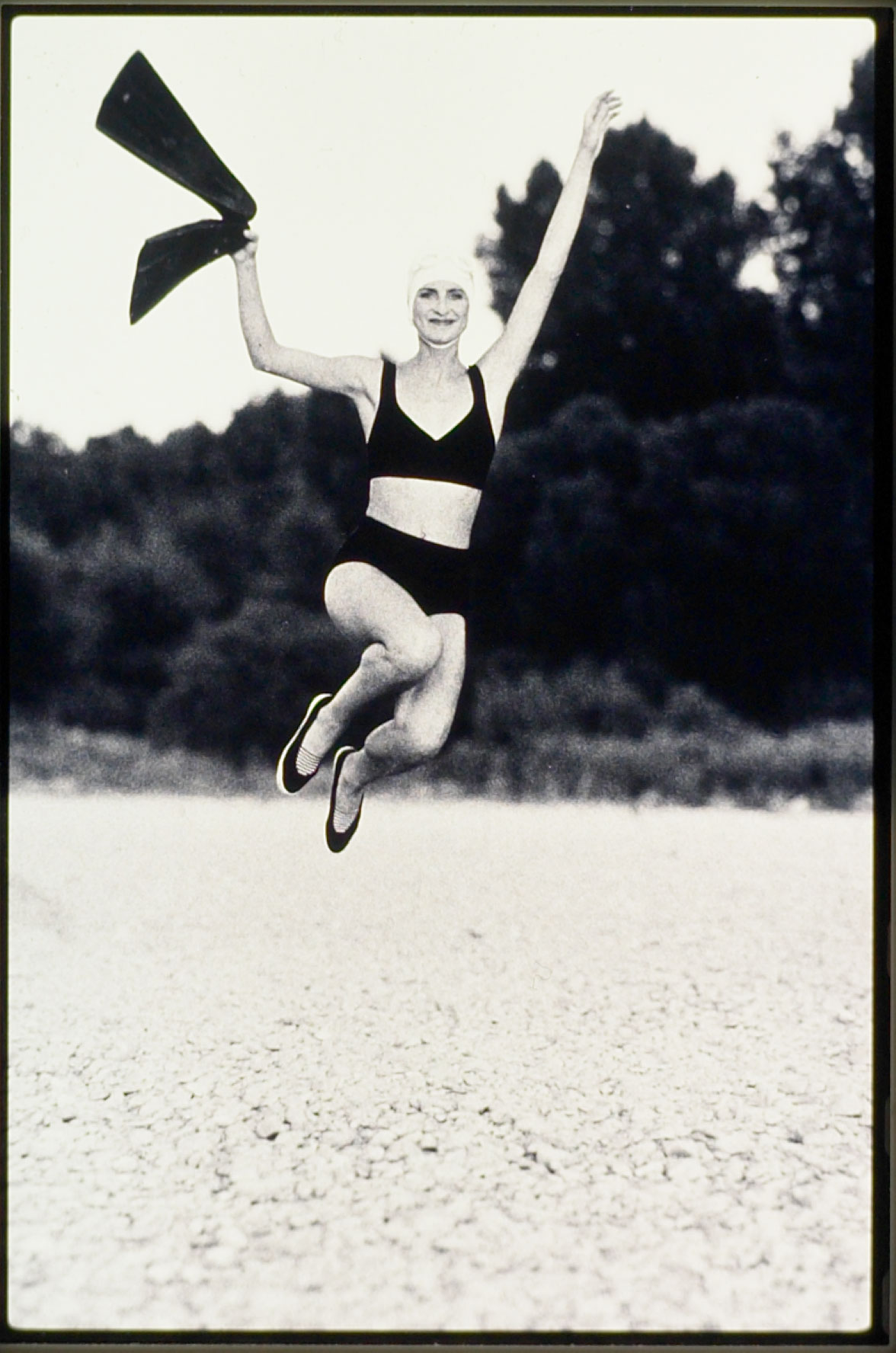 Eine junge Frau springt an einem Strand in die Luft. Sie trägt einen schwarzen Bikini und eine Badekappe. Das Foto ist analog aufgenommen und Schwarzweiss vergrößert. Fotograf: Jörg Saibou, Köln Ehrenfeld.