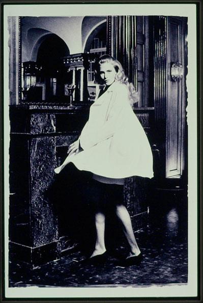 Eine Frau steht an einer Hotelrezeption. Sie trägt einen Rock und einen weißen Mantel. Das Foto ist analog aufgenommen und Schwarzweiss vergrößert. Fotograf: Jörg Saibou, Köln Ehrenfeld.