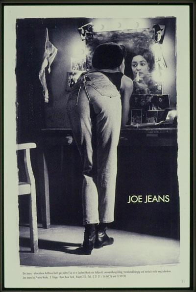 Eine Frau steht vor einem Spiegel und schminkt sich. Sie trägt eine Jeans von