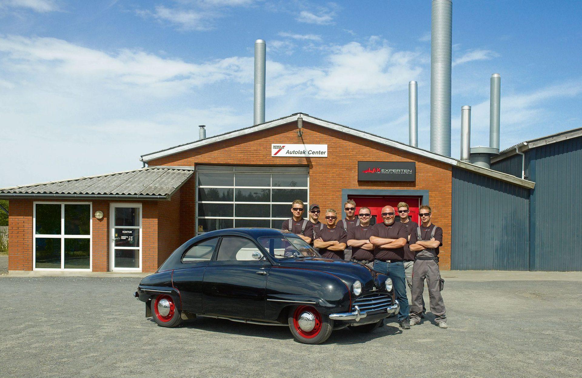 Hinter einem Oldtimer stehen mehrer Mitarbeiter einer Autolackiererei. Das Bild wurde für den Kalender Spies Hecker von Jörg Saibou fotografiert.