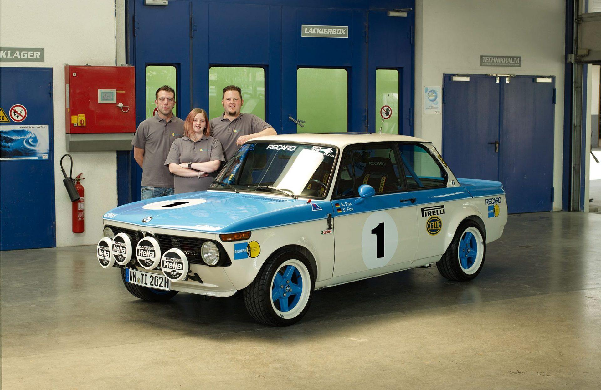 drei Menschen stehen hinter einem alten BMW mit der Nummer eins