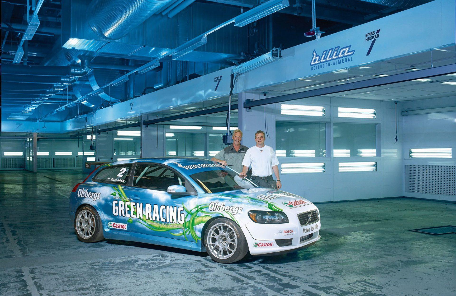 Zwei Männer stehen hinter einem Sportwagen mit der Aufschrift Green racing olsbergs