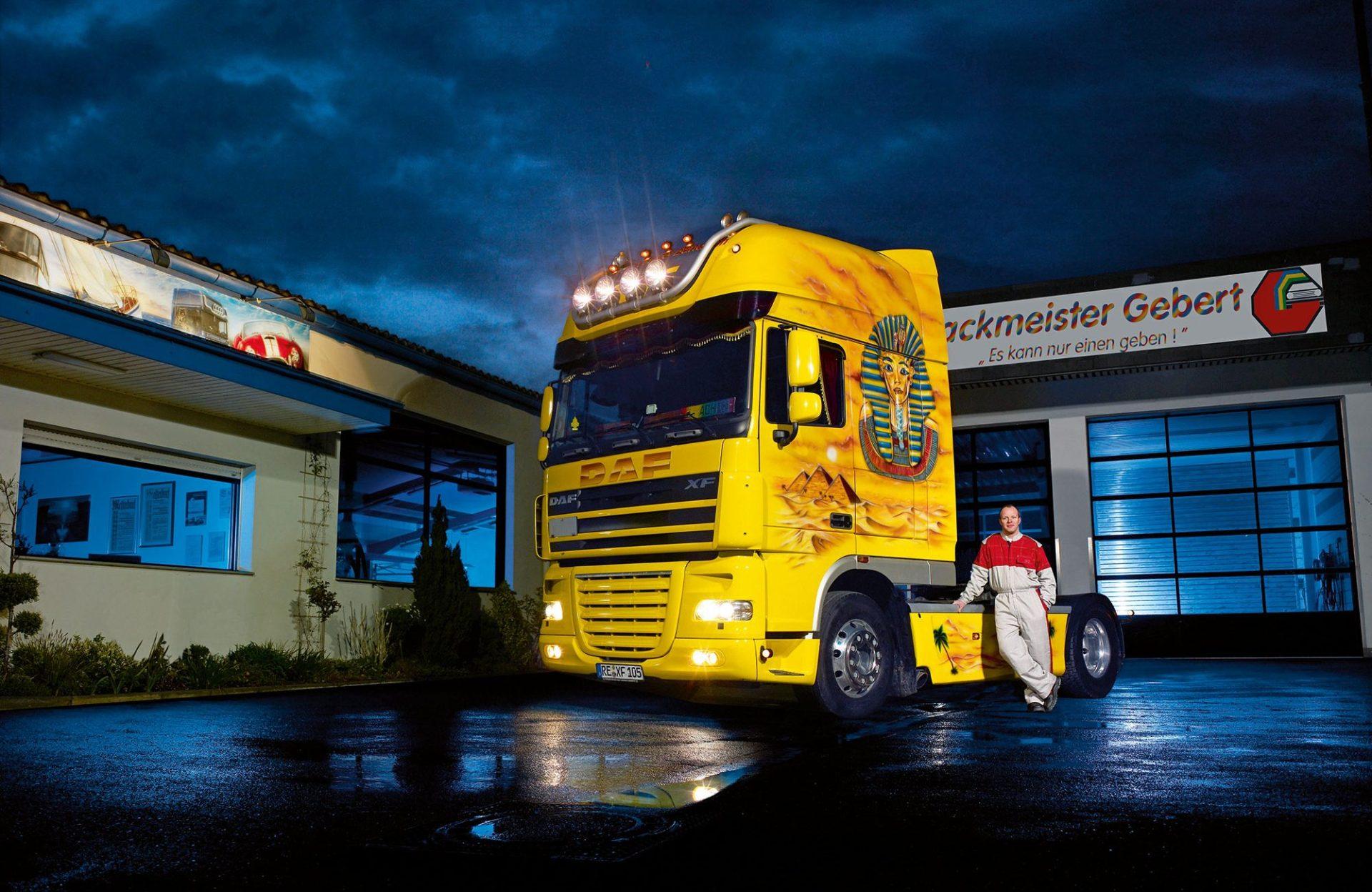 Ein gelber Truck steht nachts vor einer Garage, daneben lehnt ein Mann.