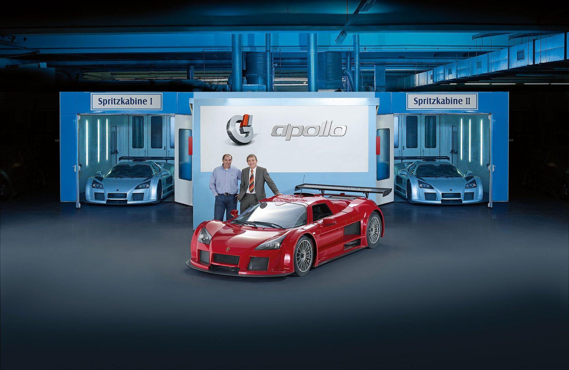 Ein roter Ferrari steht in einer Spritzkabine, dahinter stehen 2 Männer.