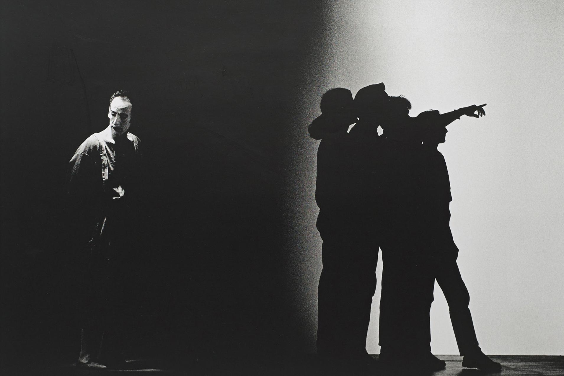 Ein Mann steht im linken Bildausschnitt, er ist ausgeleuchtet, auf der rechten Seiten befinden sich die Schatten von vier weiteren Personen.