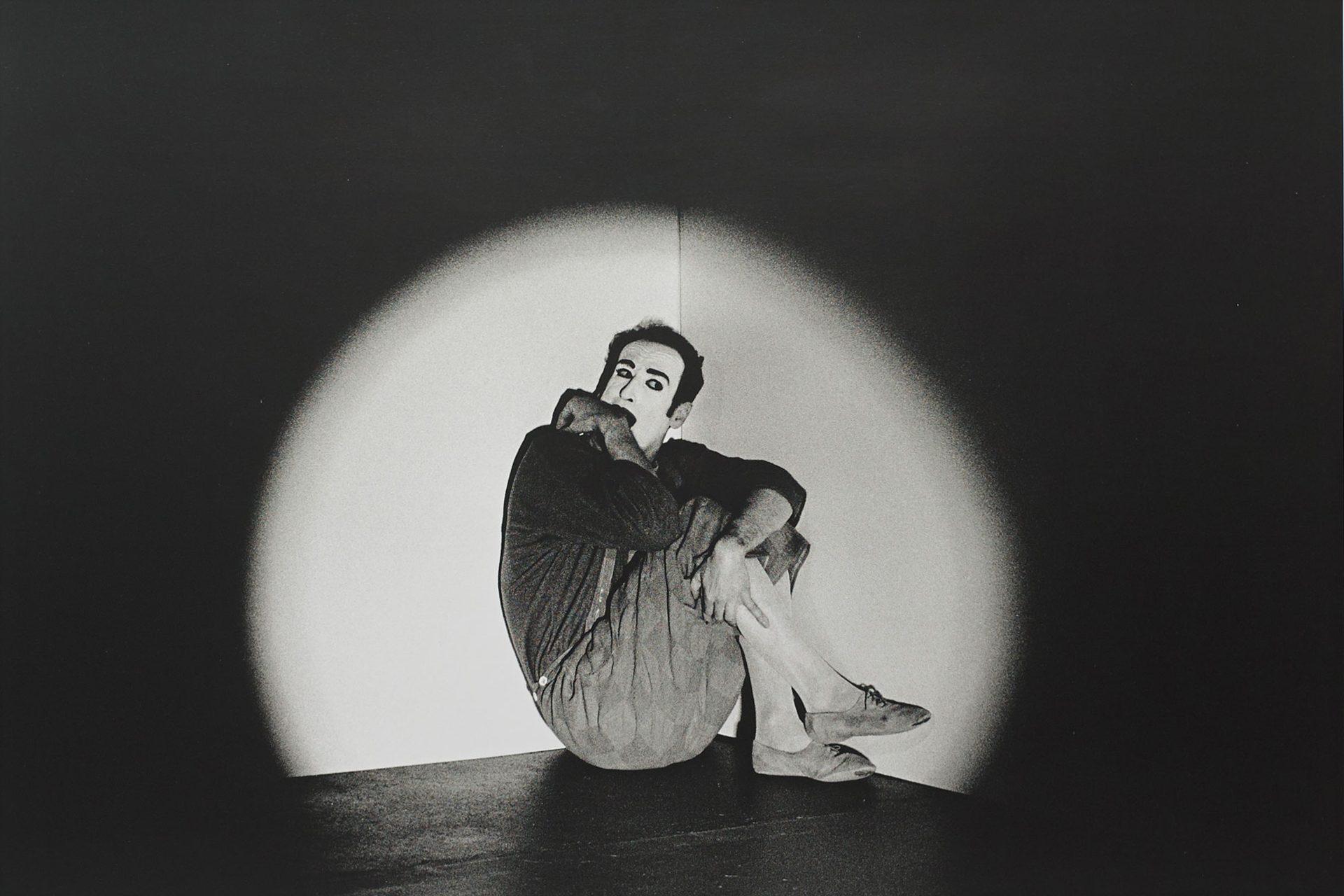 Ein Mann sitzt in einem Lichtkegel in einer Ecke. Er wirkt verängstigt und einsam.