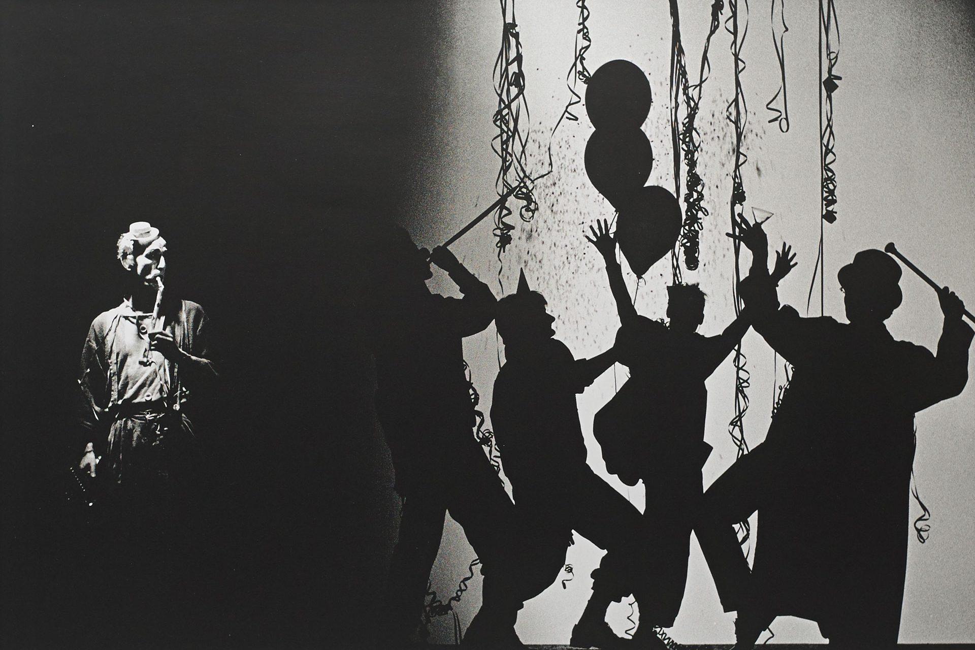 Eine Studioaufnahme, auf der linken Seite wird ein mann beleuchtet, auf der rechten Seite ist ein Schatten einer feiernden Karnevalsgesellschaft.