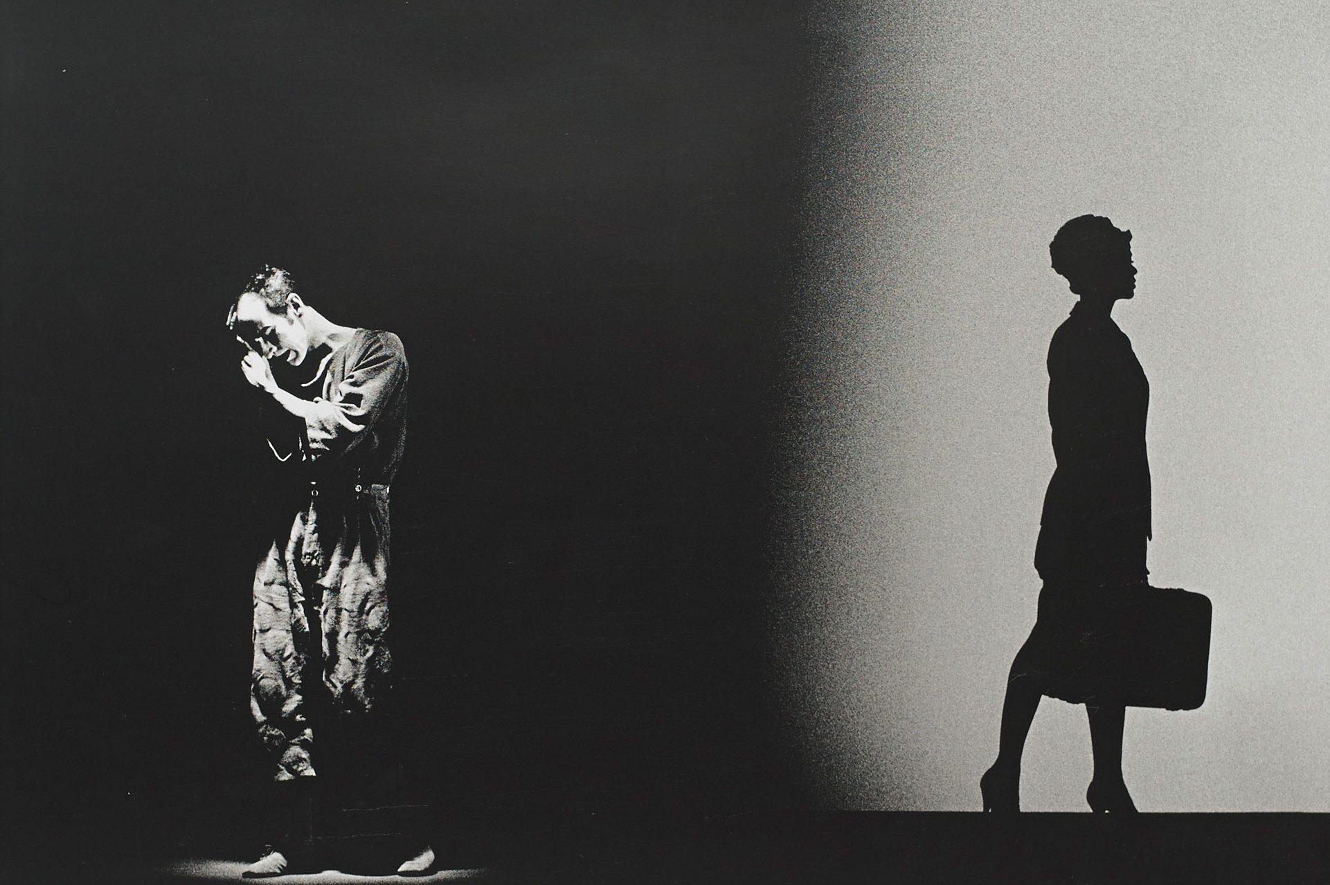 Eine Studioaufnahme, auf der linken Seite wird ein mann beleuchtet, auf der rechten Seite ist ein Schatten einer fortgehenden Frau, die einen Koffer trägt.
