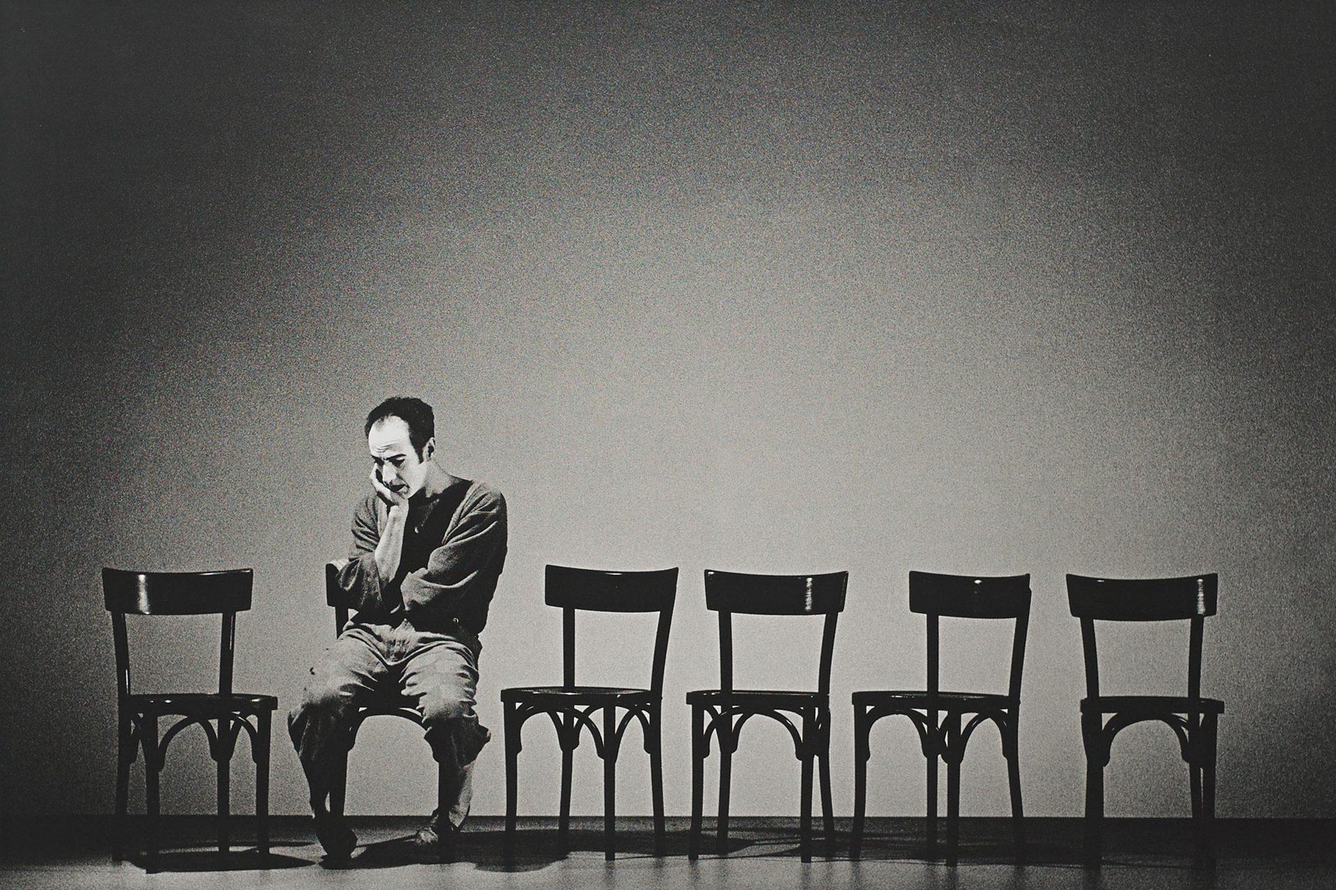 Ein Mann sitzt auf einem von sechs Stühlen. Er ist alleine und wirkt nachdenklich und traurig.