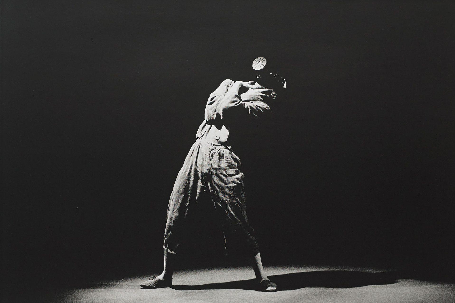 Ein Mann steht in einem Fotostudio und wird dramatisch beleuchtet.