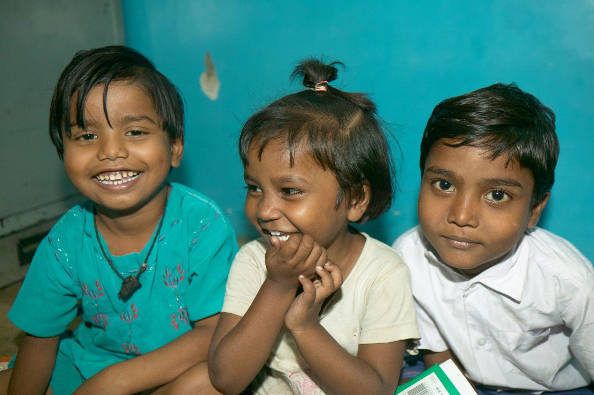 3 Kinder lachen in die Kamera, das Bild entband in einer Schule in Indien.