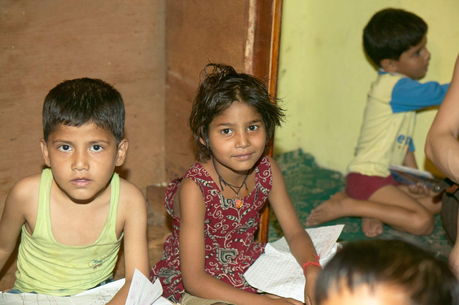 Zwei Kinder schaut in die Kamera, das Bild entband in einer Schule in Indien.