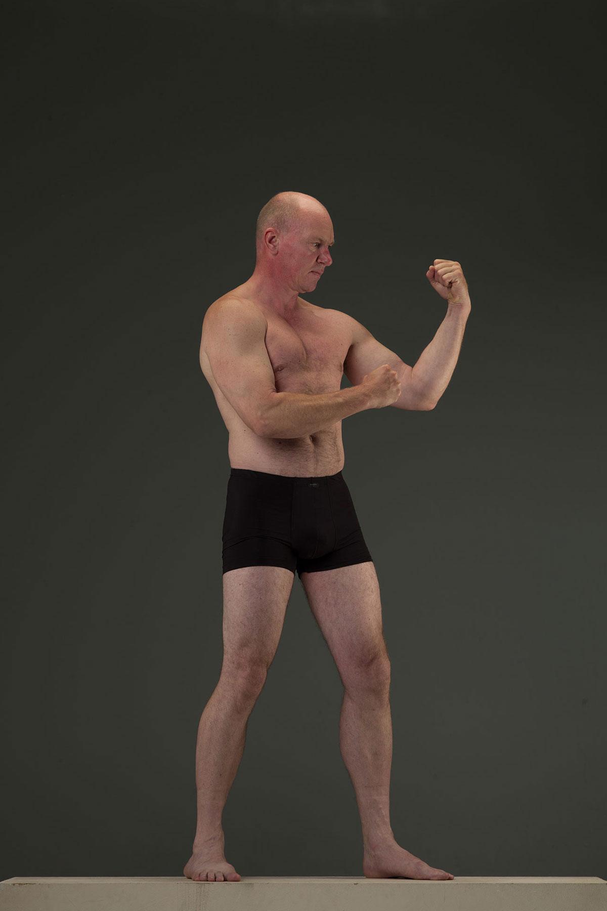 Ein Mann steht in schwarzer Boxershorts in einem Fotostudio in Köln.