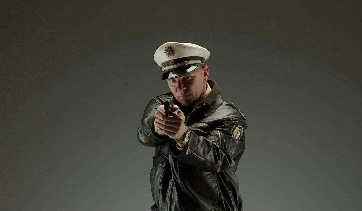 Ein Polizist steht in voller Uniform und schaut in die Kamera. Er hält eine Pistole in der Hand.