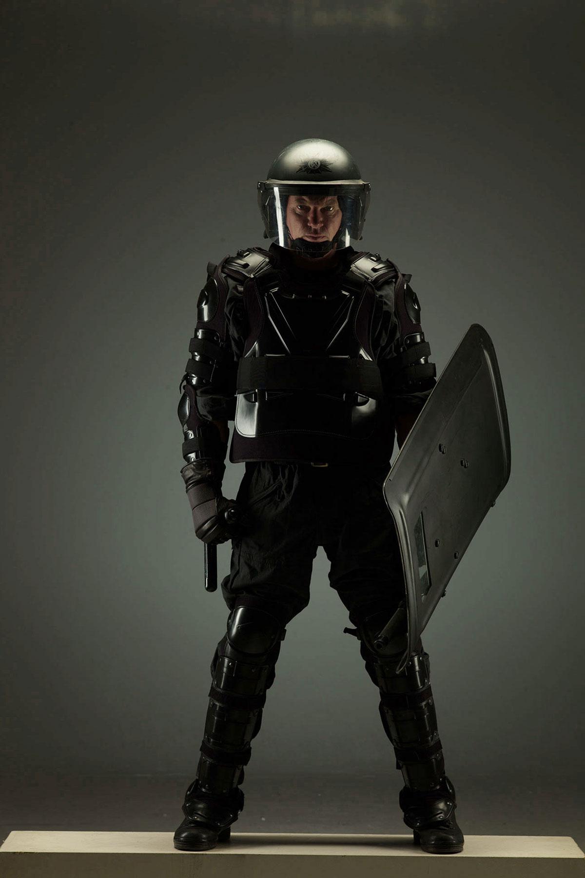 Ein Polizist steht in voller Uniform und schaut in die Kamera.
