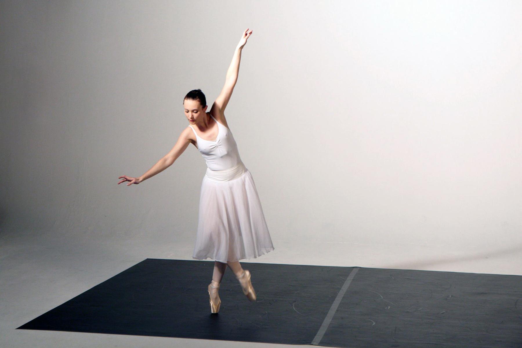 Eine Frau in einem weißen Kleid und Ballettschuhen tanzt in einem Studio. Die Bilder wurden für ein freies Filmprojekt im Studio Saibou in Köln aufgenommen.