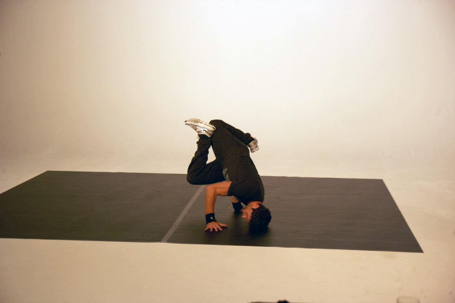 Ein Mann mit einem schwarzen Oberteil und einer schwarzen Hose tanzt in einem Studio. Die Bilder wurden für ein freies Filmprojekt im Studio Saibou in Köln aufgenommen.