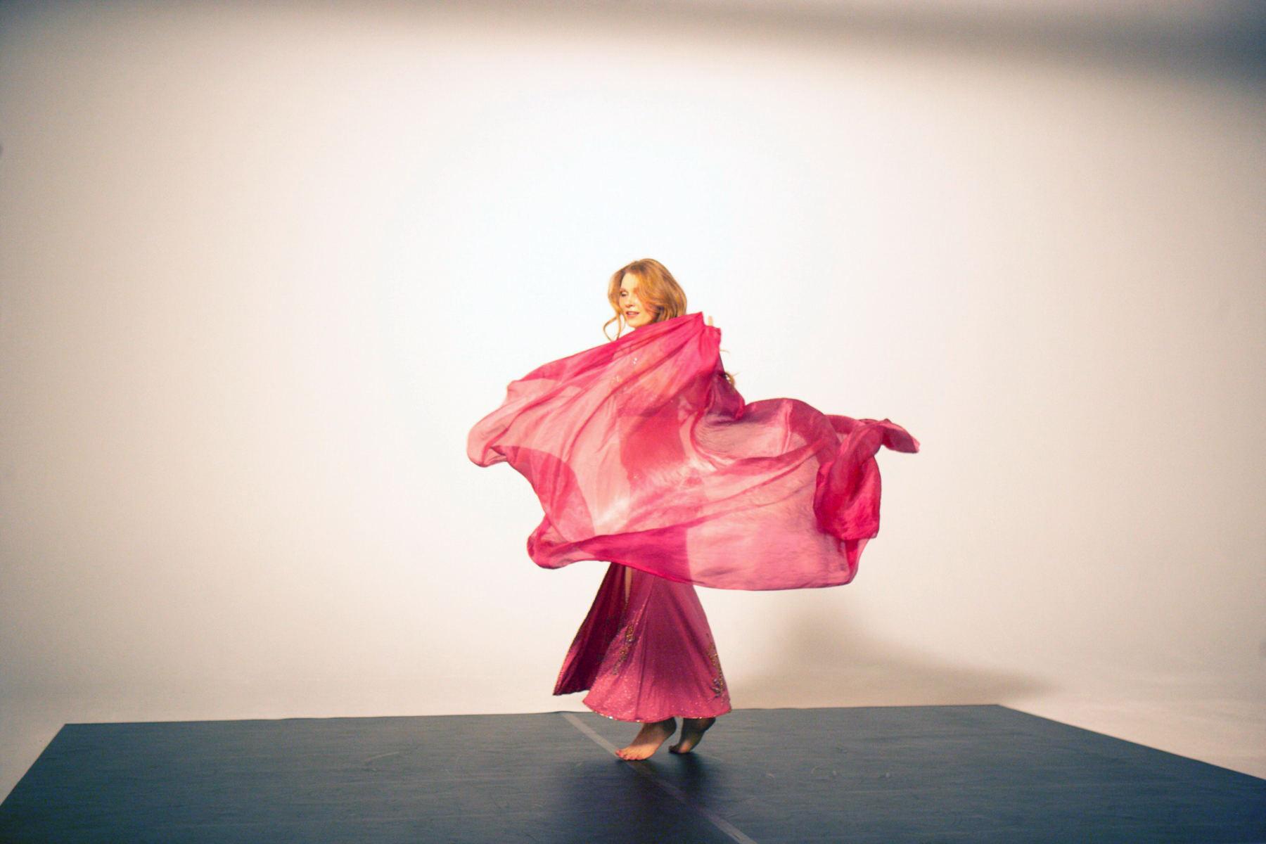 Eine Frau mit einem roten Oberteil und einem roten Kleid in einem Studio. Ein Halbdurchsichtiger Schal schwingt um sie. Die Bilder wurden für ein freies Filmprojekt im Studio Saibou in Köln aufgenommen.