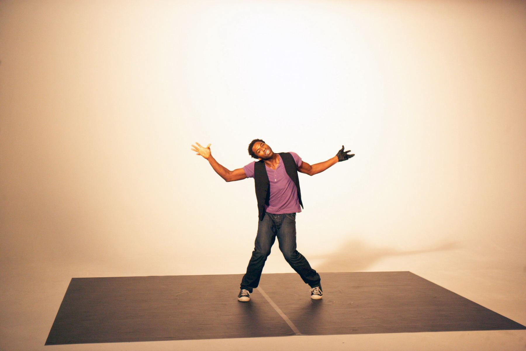 Ein Mann mit einem violetten Oberteil und einer schwarzen Hose tanzt in einem Studio. Die Bilder wurden für ein freies Filmprojekt im Studio Saibou in Köln aufgenommen.