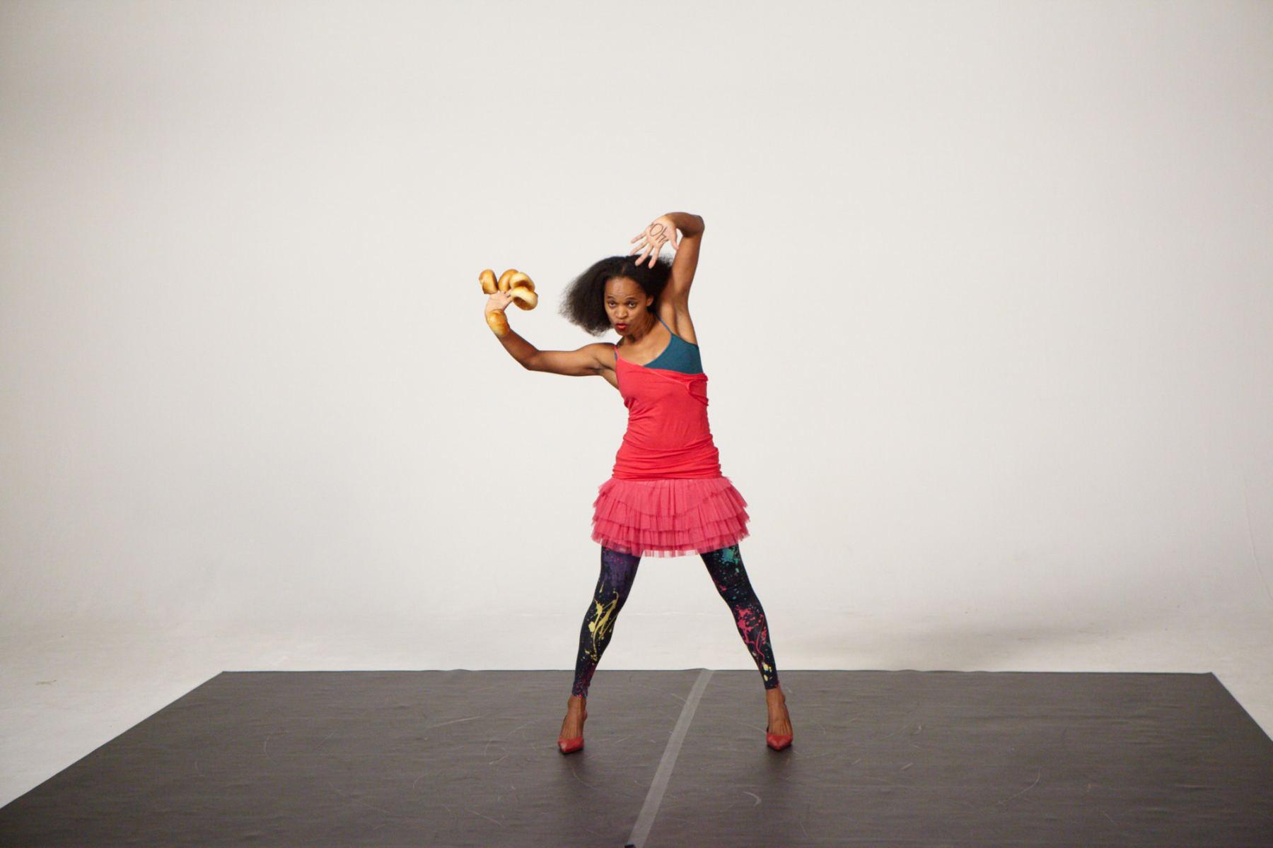 Eine Frau mit einem bunten Kleid tanzt in einem Studio. Die Bilder wurden für ein freies Filmprojekt im Studio Saibou in Köln aufgenommen.