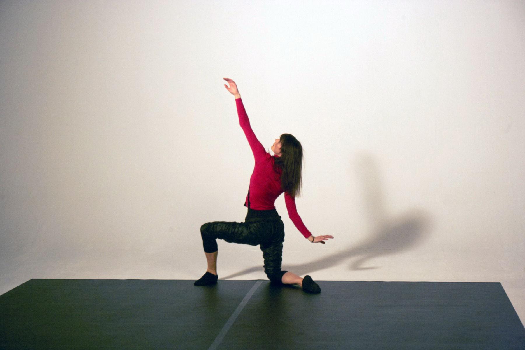 Eine Frau mit einem roten Oberteil und einer schwarzen Hose tanzt in einem Studio. Die Bilder wurden für ein freies Filmprojekt im Studio Saibou in Köln aufgenommen.