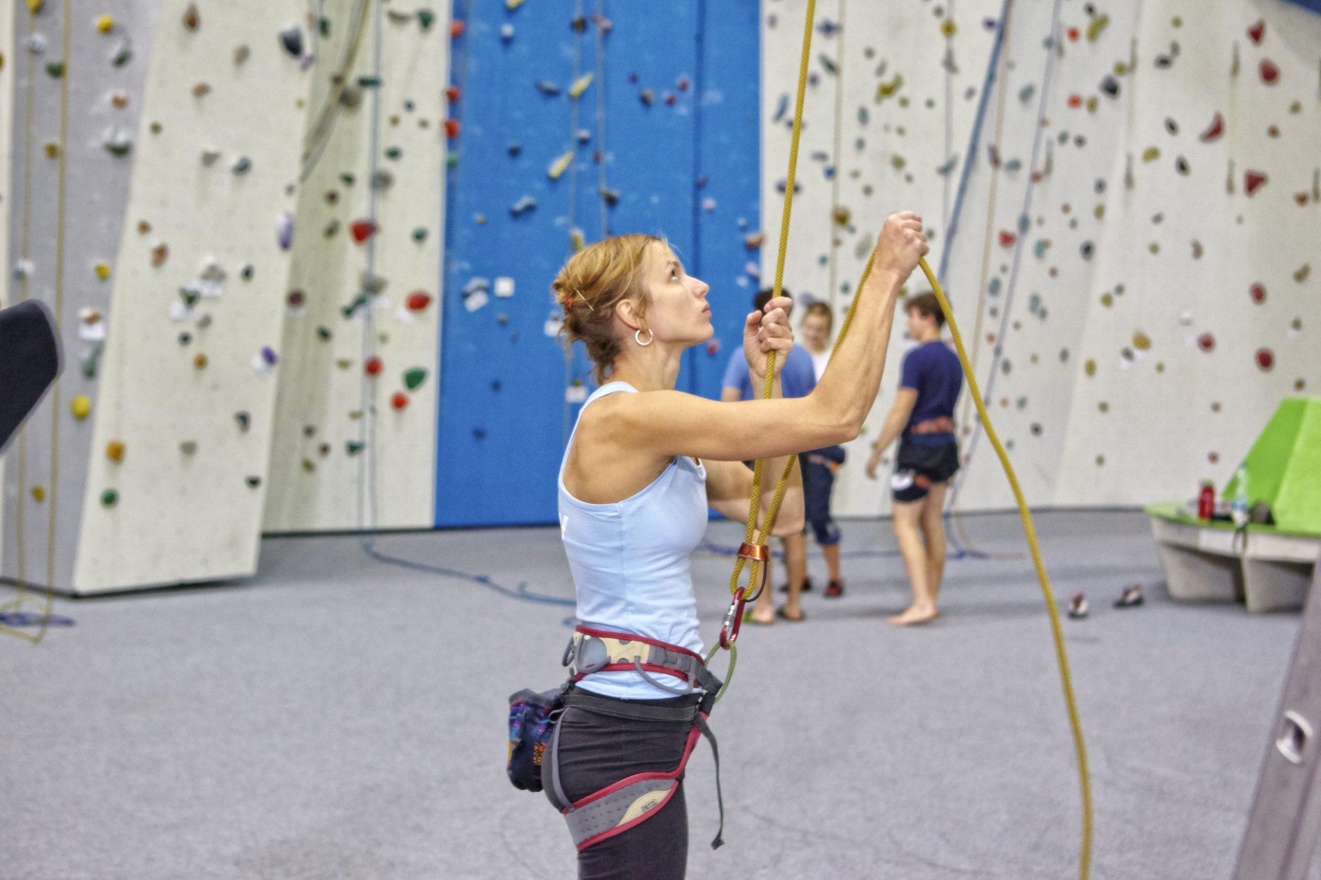 Frau sichert in der Kletterhalle jemanden. Sie trägt einen Klettergurt. Fotograf: Jörg Saibou, Köln.