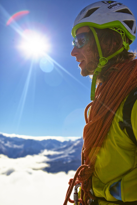 Ein Mann steht auf einem Berg, er trägt ein Klettertau um den Hals. Fotograf: Jörg Saibou, Köln.