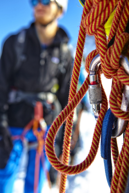 Im Fokus steht ein Klettertau und ein Karabinerhaken, dahinter steht unscharf ein Mann, der eine Kletterausrüstung trägt. Fotograf: Jörg Saibou, Köln.