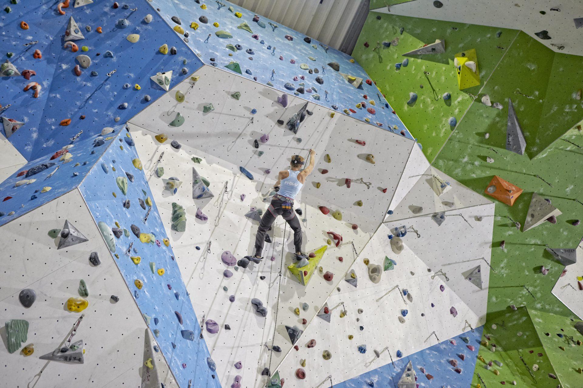 Frau klettert in einer Kletterhalle an einer Wand. Fotograf: Jörg Saibou, Köln.