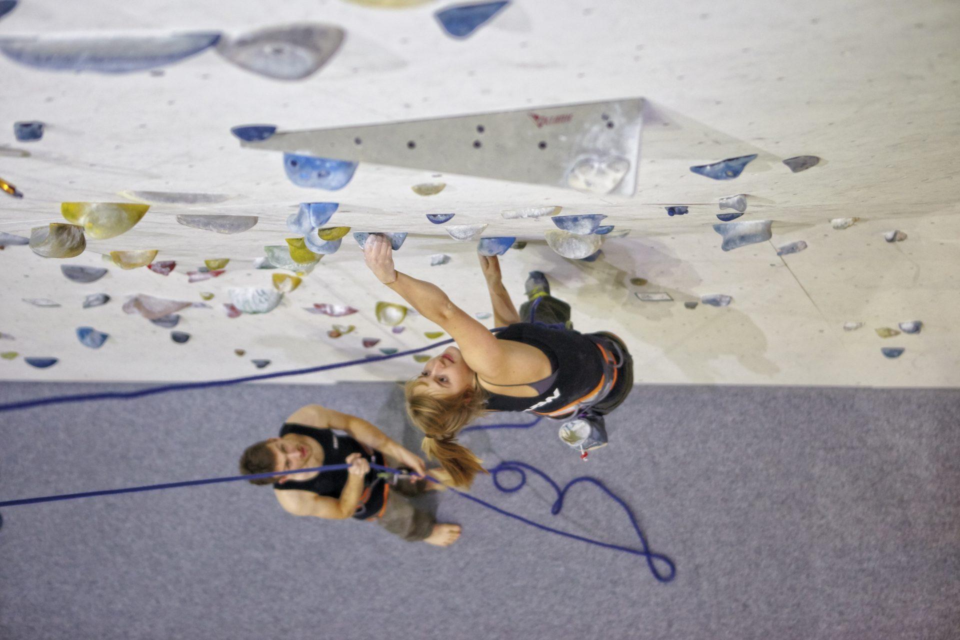 Frau klettert in einer Kletterhalle an einer Wand, sie wird von einem Mann gesichert. Fotograf: Jörg Saibou, Köln.