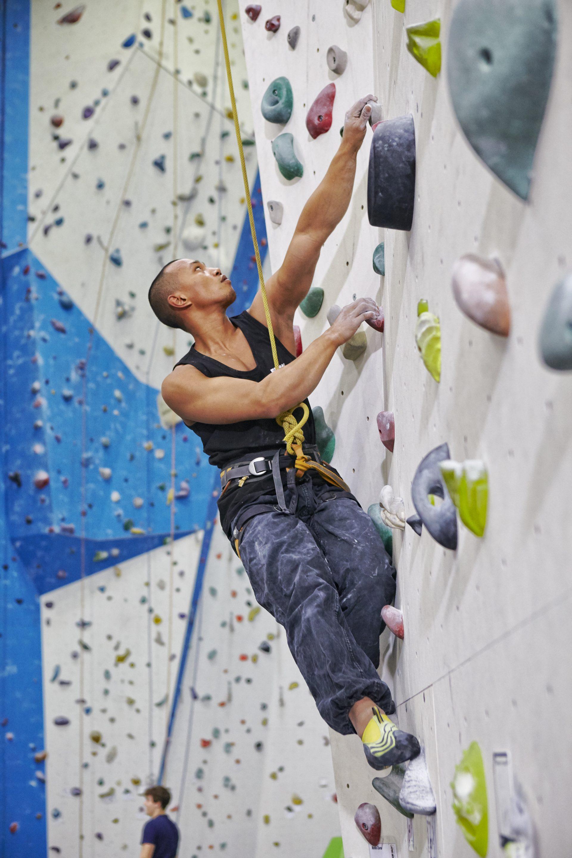 Mann klettert in einer Kletterhalle an einer Wand. Fotograf: Jörg Saibou, Köln.