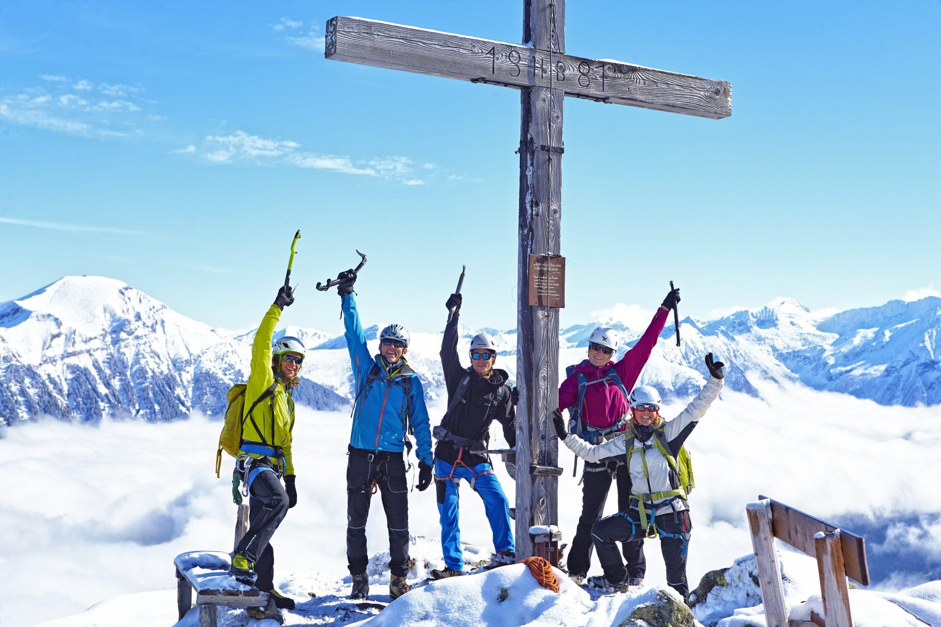 Fünf Kletterer haben sich um ein Gipfelkreuz versammelt. Fotograf: Jörg Saibou, Köln.