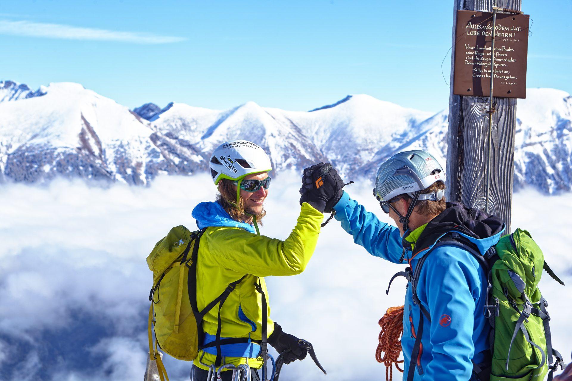 Zwei Kletterer beglückwünschen sich, sie haben gerade den Gipfel erklommen. Fotograf: Jörg Saibou, Köln.